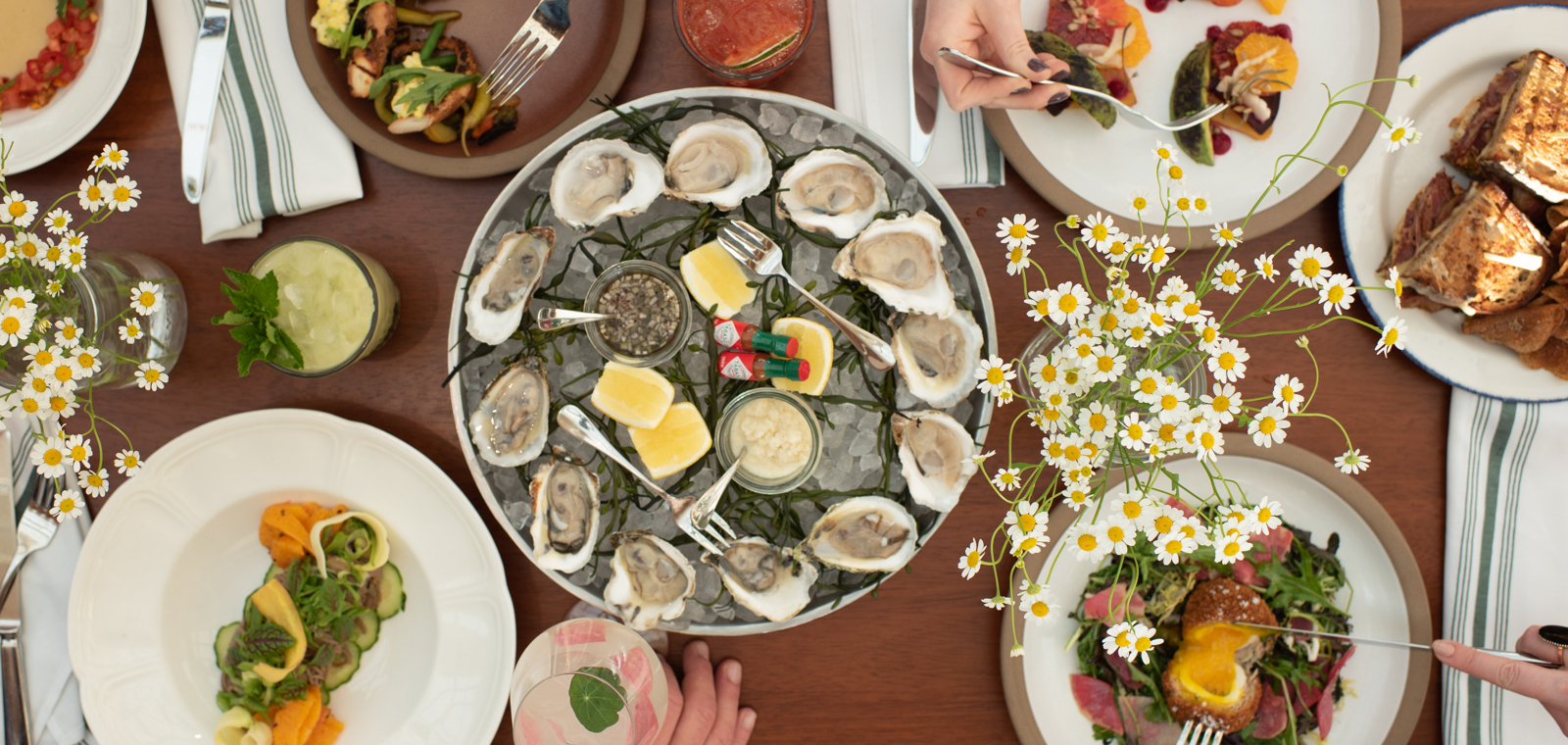 Lunch table at Cindy's; shareable fare; oysters; cocktails