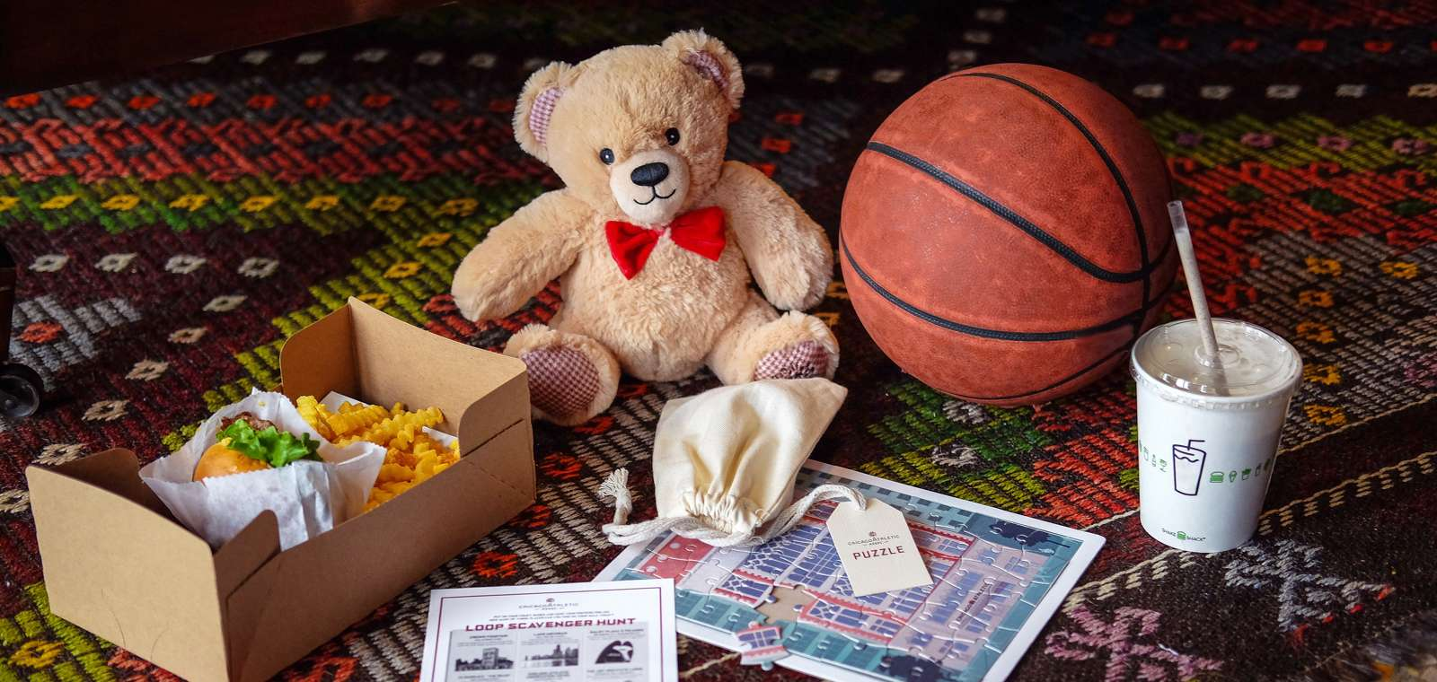 Photo to accompany Family Play & Stay package, highlighting amenities involved in the package: basketball, Shake Shack, puzzle, bingo/scavenger hunt, photographed in Founders 328