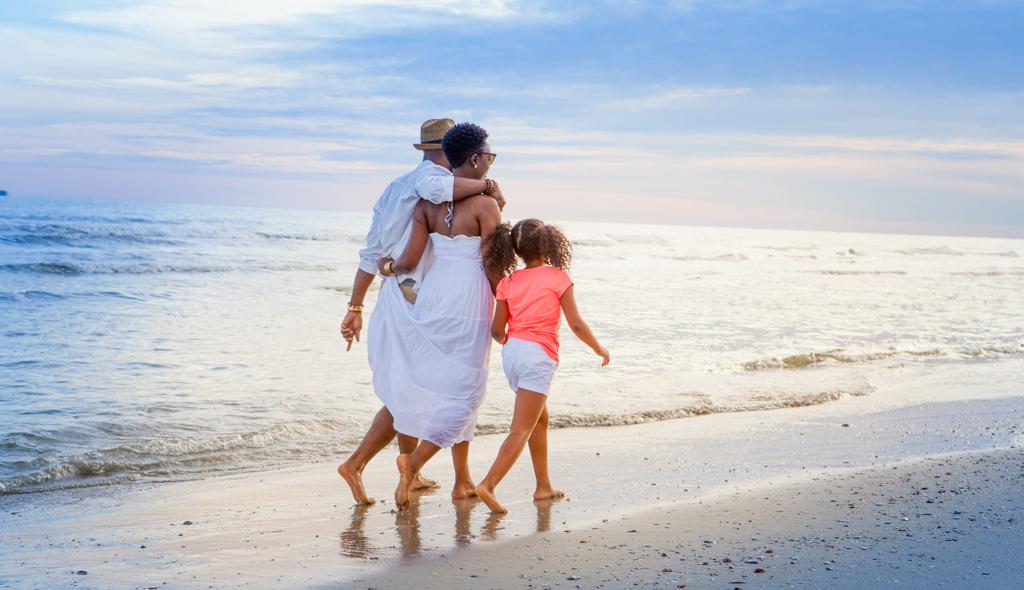 family walking on beach, bright blue