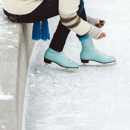 Close up on woman tying the laces of her baby blue figure skates.