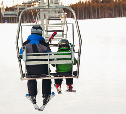 Small boy and his father sitting on a chair lift in late afternoon light in winter, viewed from behind