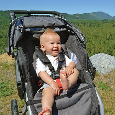 Smiling baby boy in stroller with mountains SZ100