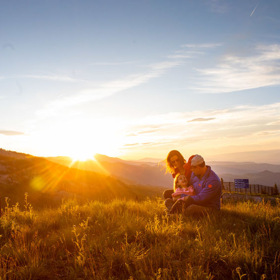 A family enjoys the summer sunset from atop Snowmass mountain
