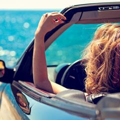 Woman parked in a convertible overlooking ocean