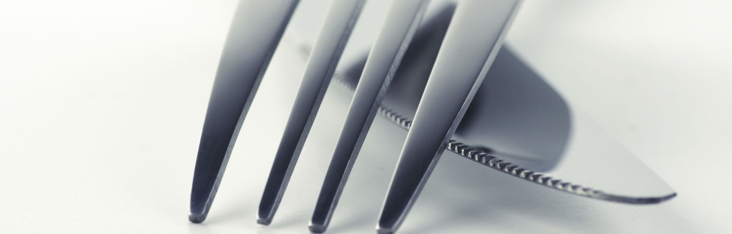 Close-up of fork and knife on white background. Soft focus, shallow DOF. Toned image.