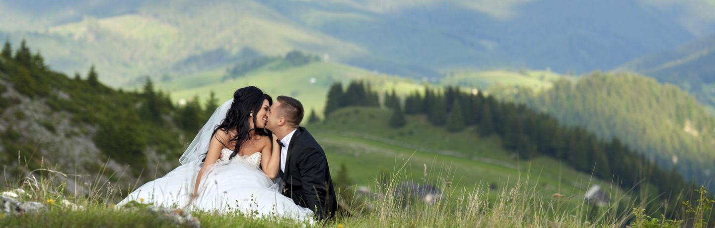 bride and groom in idyllic landscape kissing and loving, romantic moment in nature.