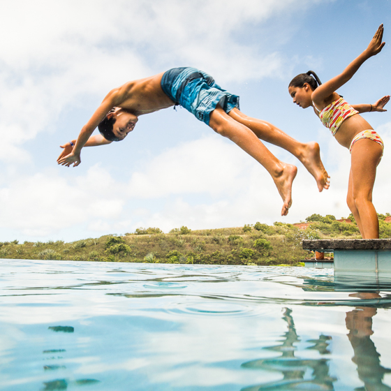 A boy and girl diving from a dock into clear aquamarine water with blue sky and clouds.