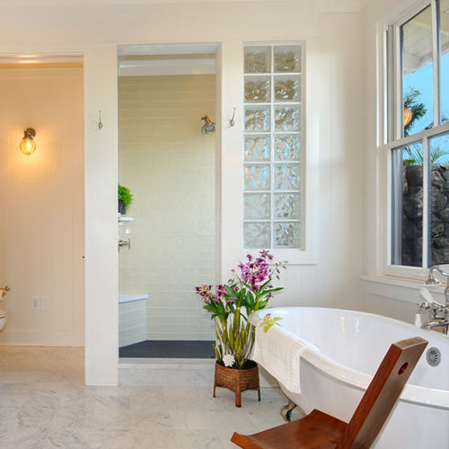 Clean, modern white bathroom with soaking tub, marble double vanities, walk-in shower and marble flooring. Large windows look out to handcrafted Hawaiian rock wall to outdoor shower.