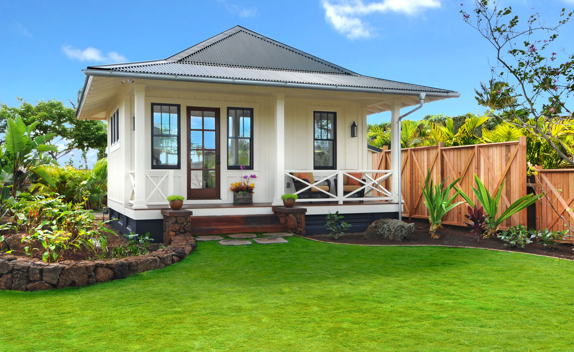 Exterior view of white plantation style one-bedroom Ohana. Surrounded by lush landscaping.