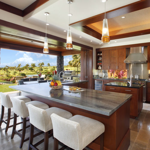 Modern open chef's kitchen with island and L-shaped counter lined with four bar stools. Entire wall slides open to covered lanai, plunge pool, and outdoor seating.