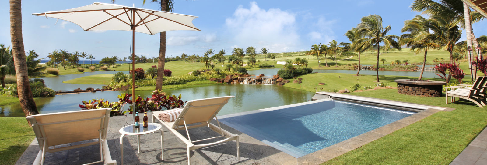 Luxurious tropical pool setting off lanai with two lounge chairs and umbrella. View over golf course lakes and fairway to ocean.