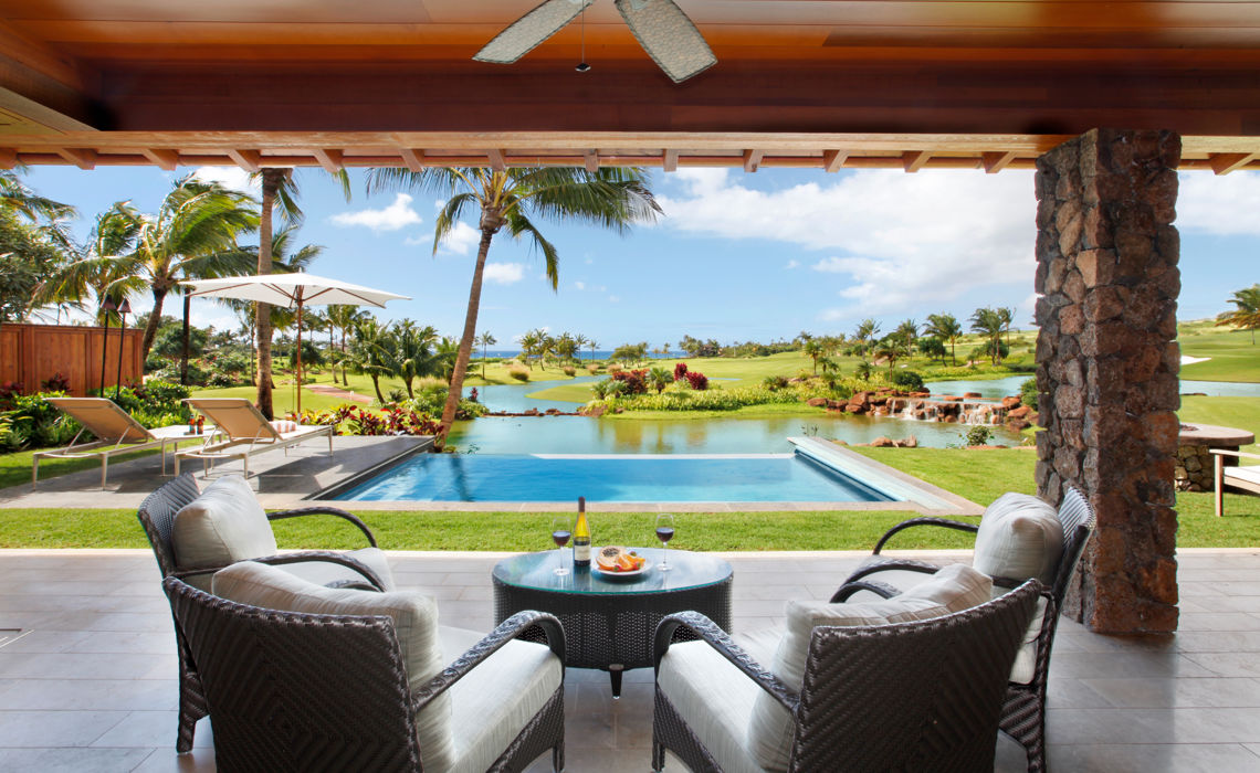 View from open lanai seating out over plunge pool to golf course lakes and fairway down to ocean.