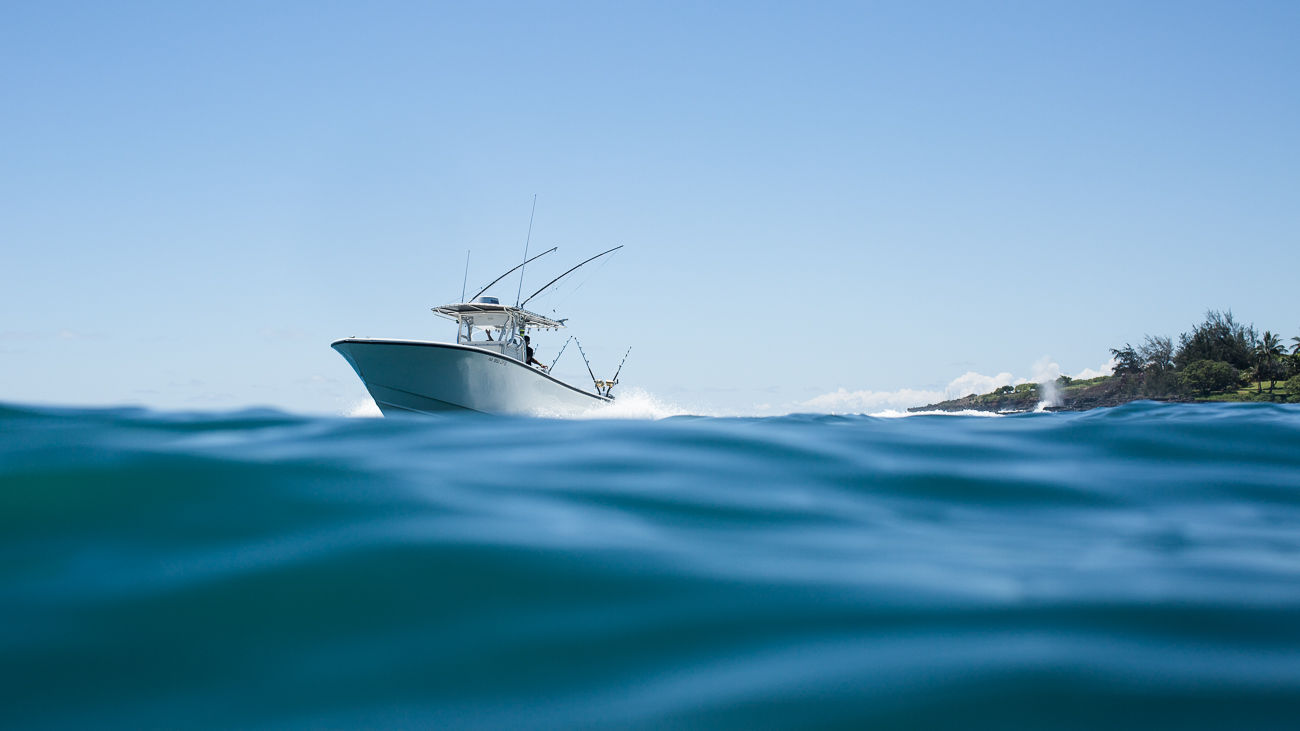 The Kukui'ula sport fishing and leisure motor boat in Kukui'ula Harbor pulling into the dock.
