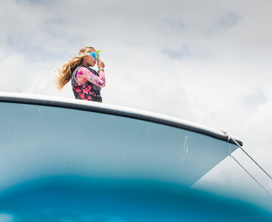 A girl in a long-sleeve rash guard and snorkel mask standing at the front of the boat. View from the water looking up at the boat.