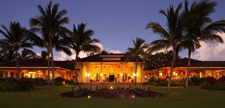 Panoramic view across lawn of warm glow of lights in the Kukui'ula Club House at dusk.