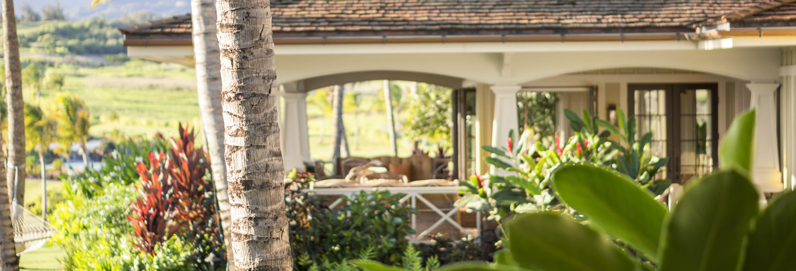 Looking through the lush foliage across the lawn to the open air seating of the Kukui'ula Club House restaurant.