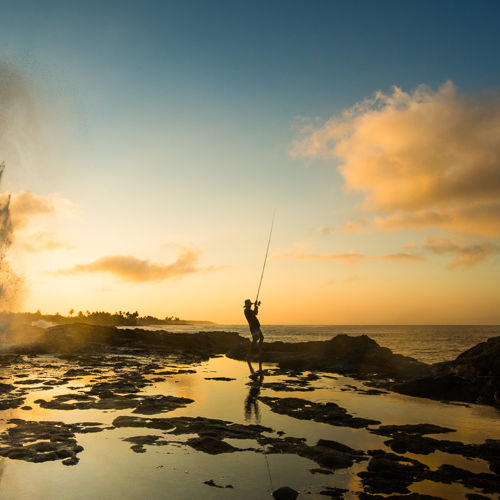 Powerful ocean blowhole Spouting Horn across from Kukui'ula Harbor Beach at sunrise with fisherman pulling in a catch.