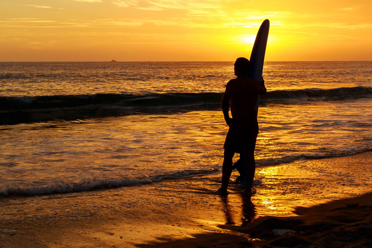surfer stands on beach admiring the colorful sunset