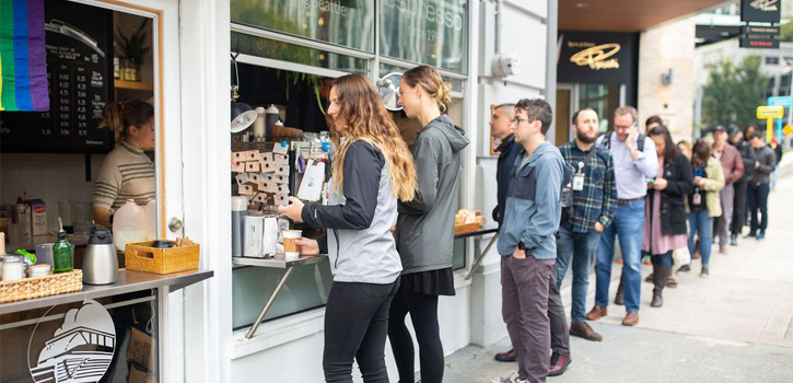 A couple stands in line ordering food at a coffee shop.