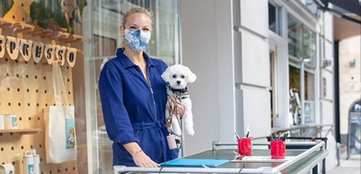 A woman holds a small white dog while wearing a mask.