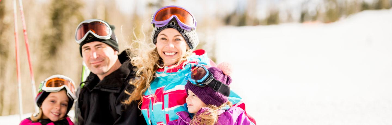 Family Sitting On Ski Slope