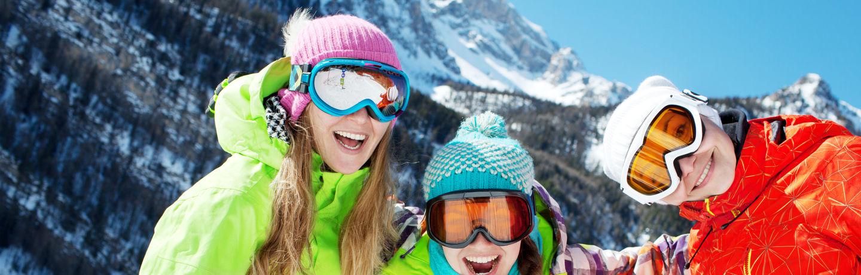 Three Kids Smiling In Ski Gear