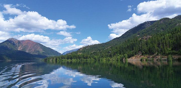 sky reflecting off a lake near mountains