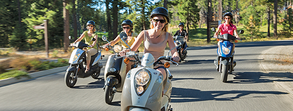 women riding mopeds together