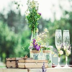 beautiful vintage wedding ceremony outdoors. Summertime. Old white wooden house. Tree decorated with white cages full of flowers. rustic style table with two glasses of cold champagne