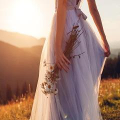 Bride wearing blue wedding dress holding bouquet in mountains at sunset. Woman walking on meadow in chamomile flowers