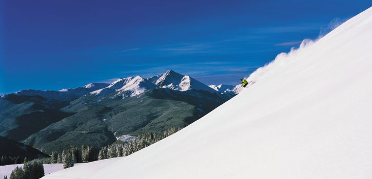 Downhill Skier On Snow Covered Slope