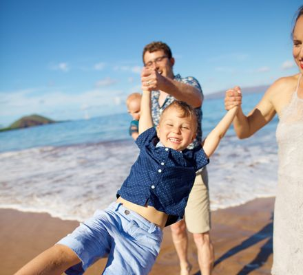 Boy playing with parents at beach