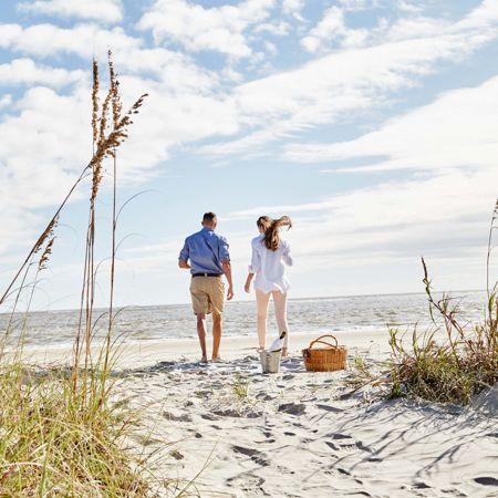young couple enjoying a beach side picnic