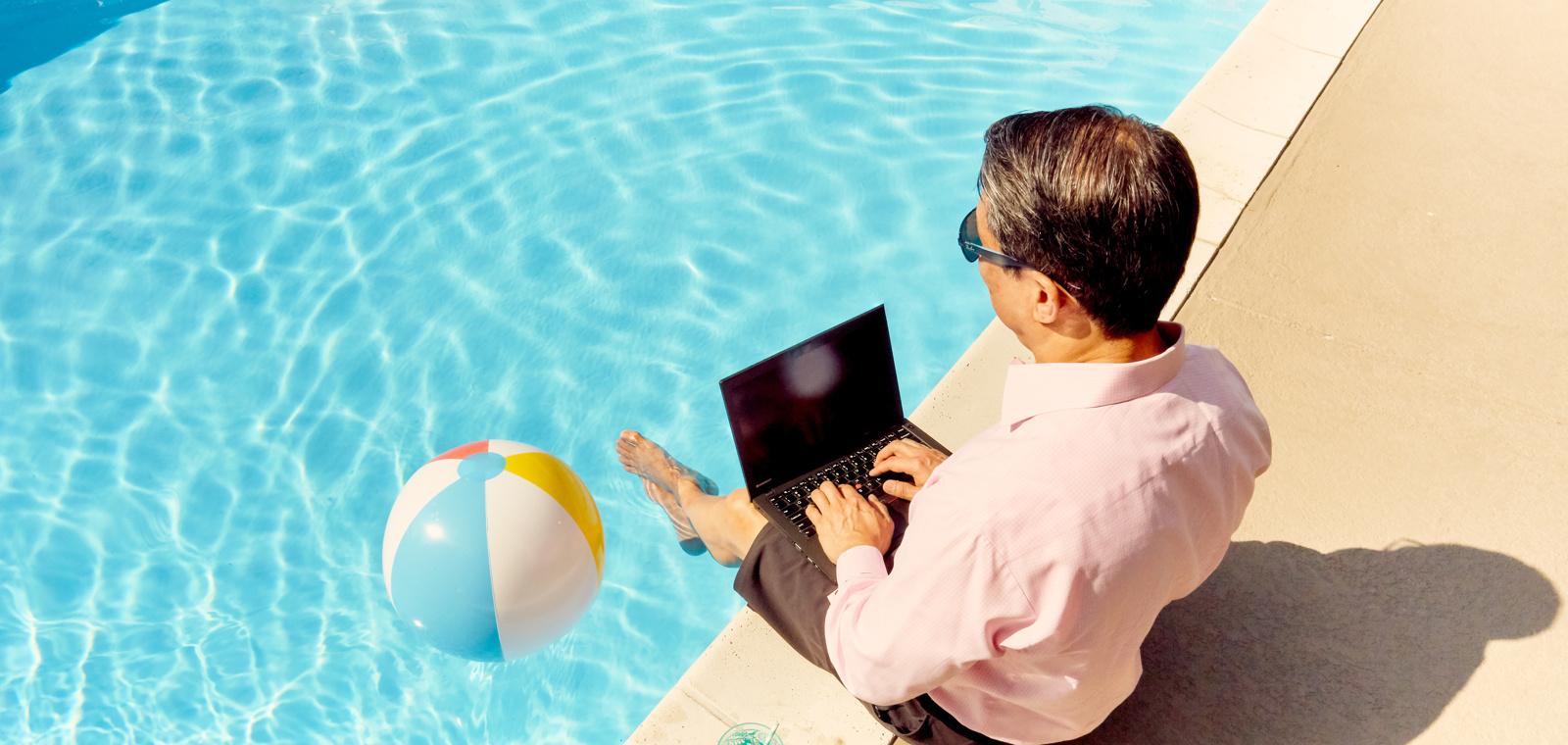 Man working on Laptop Poolside