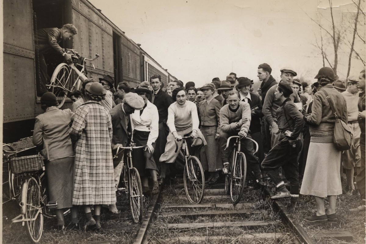 Black and White Photo of a Couple Biking in a Crowd
