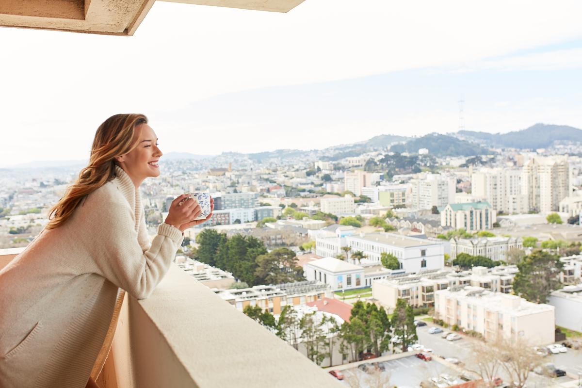 Woman Standing on Balcony with Mug of Coffee