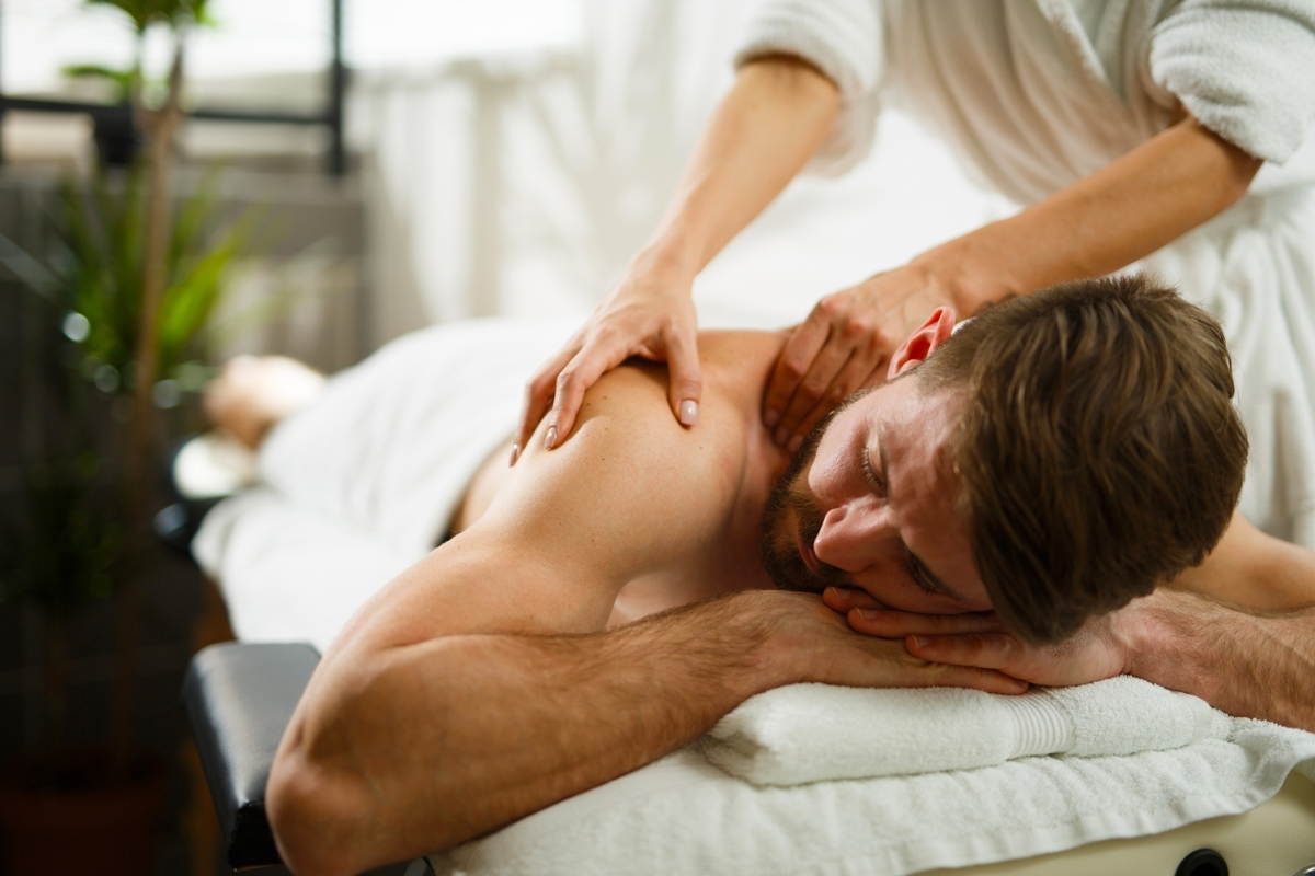 Man having back massage in the health spa. Copy space.