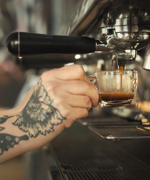 Tattooed barista making espresso in modern coffee machine. Closeup of female hand preparing bracing beverage. Small business and professional coffee brewing concept